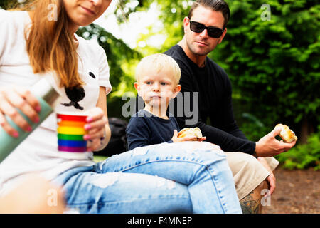 Parents and son having meal in park - Stock Photo