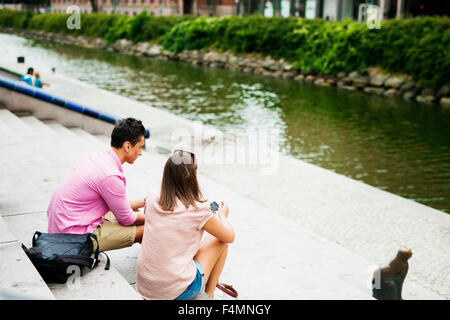 High angle view of friends sitting on steps by river - Stock Photo