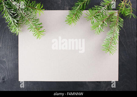 Blank sheet of paper and pine branches on the dark wooden table - Stock Photo