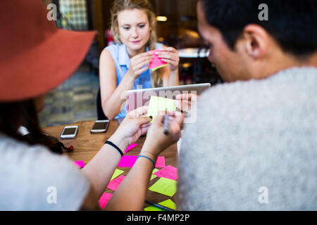 Friends writing on adhesive note while doing freelance work at cafe - Stock Photo