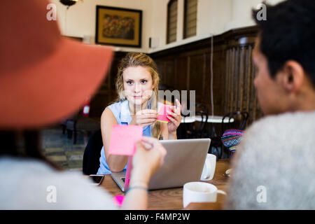 Friends holding adhesive notes while doing freelance work at cafe - Stock Photo