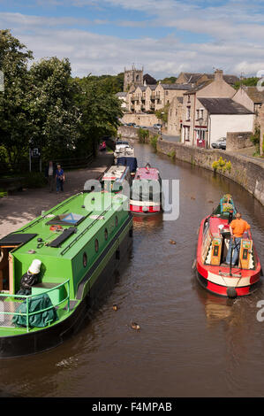 Sunny summer, view of people relaxing on canal towpath, boats moored & 1 man steering boat away -  Leeds-Liverpool - Stock Photo