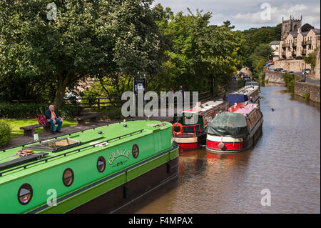 Sunny summer, high view of canal boats moored and people relaxing on towpath - Springs Branch, Leeds-Liverpool Canal, - Stock Photo