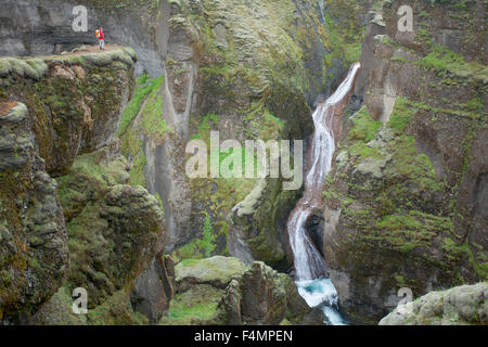 Person dwarfed by a waterfall in the Fjadrargljufur Canyon, Sudhurland, Iceland. - Stock Photo
