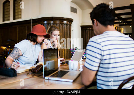 Friends doing freelance work at cafe table - Stock Photo