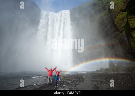 Family in the rainbow beneath 60m-high Skogafoss waterfall, Skogar, Sudhurland, Iceland. - Stock Photo