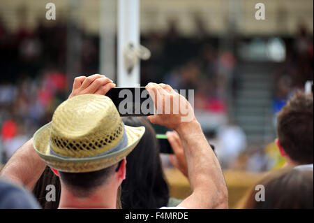 The crowd use cameras and smartphones to take photos at the Goodwood Festival of Speed in the UK. - Stock Photo