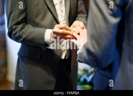 Man putting on ring on partner - Stock Photo