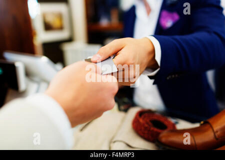 Cropped hands of customer giving credit card to cashier in clothing showroom - Stock Photo