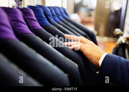 Cropped image of salesman's hand examining suit in showroom - Stock Photo