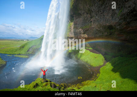 Person and rainbow beneath 60m-high Seljalandsfoss waterfall, Sudhurland, Iceland. - Stock Photo