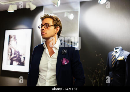Thoughtful male designer standing in showroom - Stock Photo