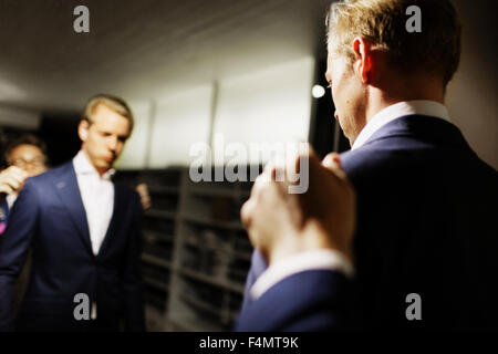 Sales clerk adjusting customer's suit in front of mirror at clothing store - Stock Photo