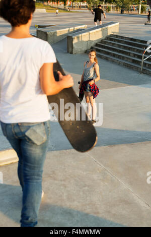 High angle view of teenage girl looking at female friend in skate park - Stock Photo
