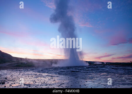 Strokkur geyser errupting at sunset, Geysir, Sudhurland, Iceland. - Stock Photo