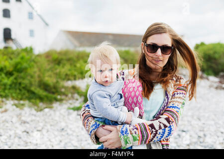 Mother in sunglasses holding son on grassy field - Stock Photo