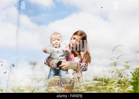 Portrait of son with mother on beach against cloudy sky - Stock Photo