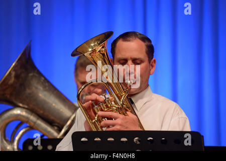 A flugel horn player gives his best in the brass band - Stock Photo