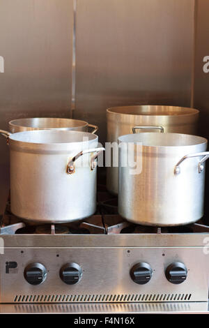 large pot on a stainless steel gas stove in a Restaurant Kitchen - Stock Photo