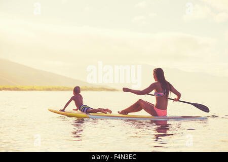 Mother and son stand up paddling at sunrise, Summer fun outdoor lifestyle