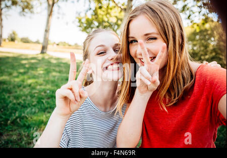 Two playful teenage girls making victory sign - Stock Photo