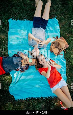 Three teenage friends with smartphones lying on blanket - Stock Photo