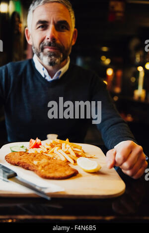Man in restaurant having Wiener Schnitzel with French fries - Stock Photo