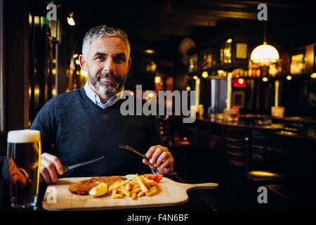 Smiling man in restaurant having Wiener Schnitzel with French fries - Stock Photo