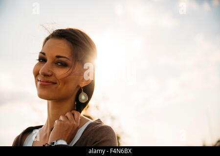 Portrait of smiling young woman at backlight - Stock Photo