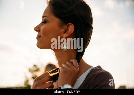 Profile of smiling young woman at backlight - Stock Photo