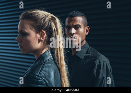 Black dressed young couple in front of black facade - Stock Photo