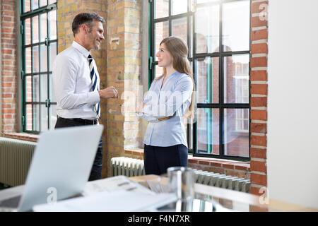 Mature man and woman talking in office - Stock Photo