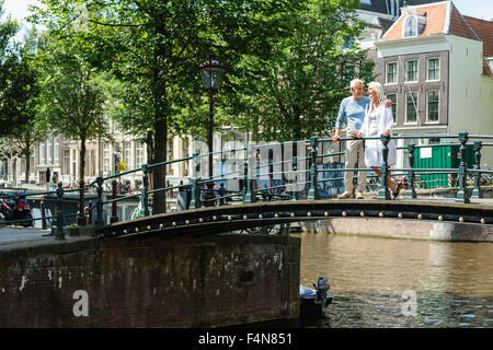 Netherlands, Amsterdam, senior couple walking on a bridge - Stock Photo