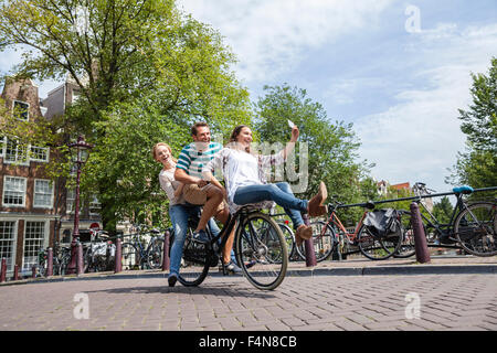 Netherlands, Amsterdam, three playful friends riding on one bicycle in the city - Stock Photo