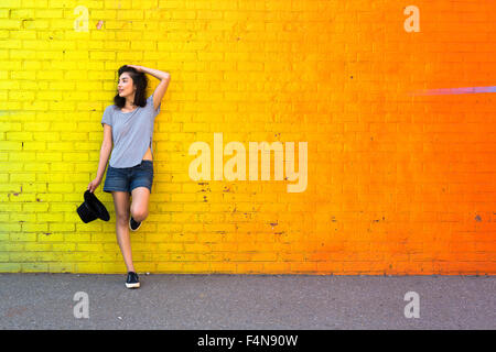 Young woman leaning against yellow brick wall - Stock Photo