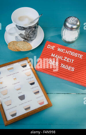Bisvuits and cup of coffee with chart of coffee sorts and text 'most important meal of the day' - Stock Photo