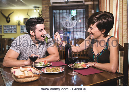Couple in restaurant eating salad and playing with food - Stock Photo