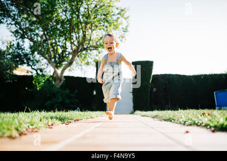 Excited little boy running barefoot on floor plates in the garden - Stock Photo
