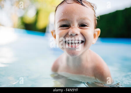 Portrait of happy little boy in a paddling pool - Stock Photo