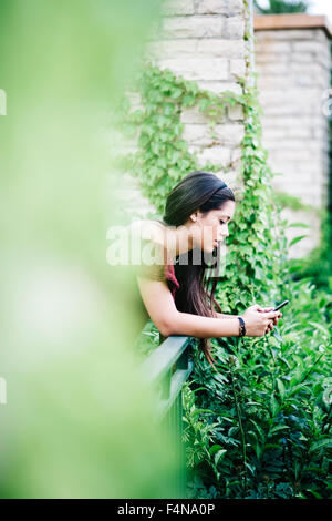 Young woman leaning on railing using cell phone - Stock Photo