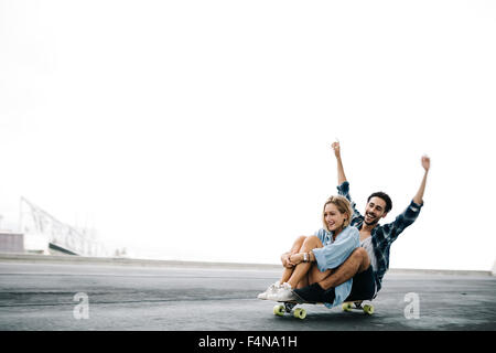 Young couple cruising on a longboard - Stock Photo