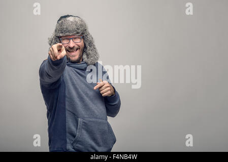 Laughing jovial man wearing glasses and a furry winter hat standing pointing at the camera with a playful expression, over grey