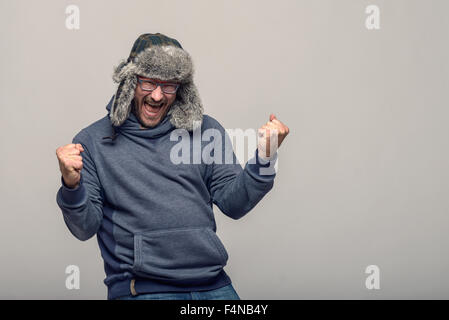 Happy man wearing glasses and a winter hat cheering and celebrating raising his clenched fists in the air with an - Stock Photo