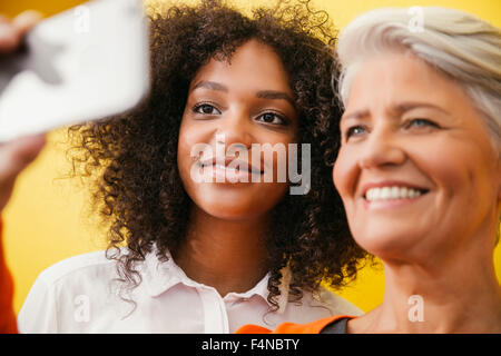 Two women taking a selfie with smartphone in front of a yellow wall - Stock Photo
