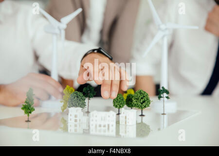 Close-up of business people wind turbine model and houses on conference table - Stock Photo