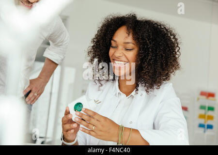Smiling female scientist holding green plug socket in lab - Stock Photo