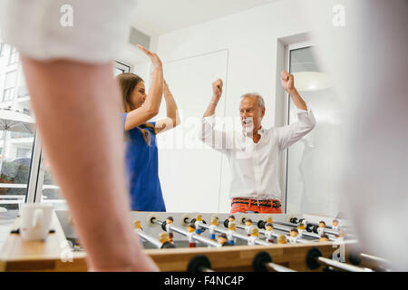 Office colleagues playing foosball during break - Stock Photo