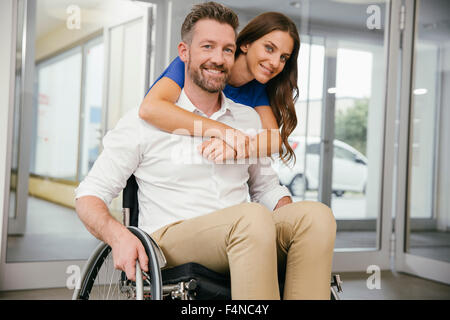 Man in wheelchair with his girlfriend, embracing happily - Stock Photo