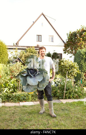 Portrait of man standing in the garden presenting red cabbage - Stock Photo
