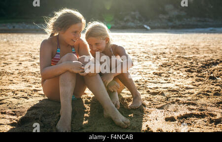 Two sisters having fun together on the beach - Stock Photo